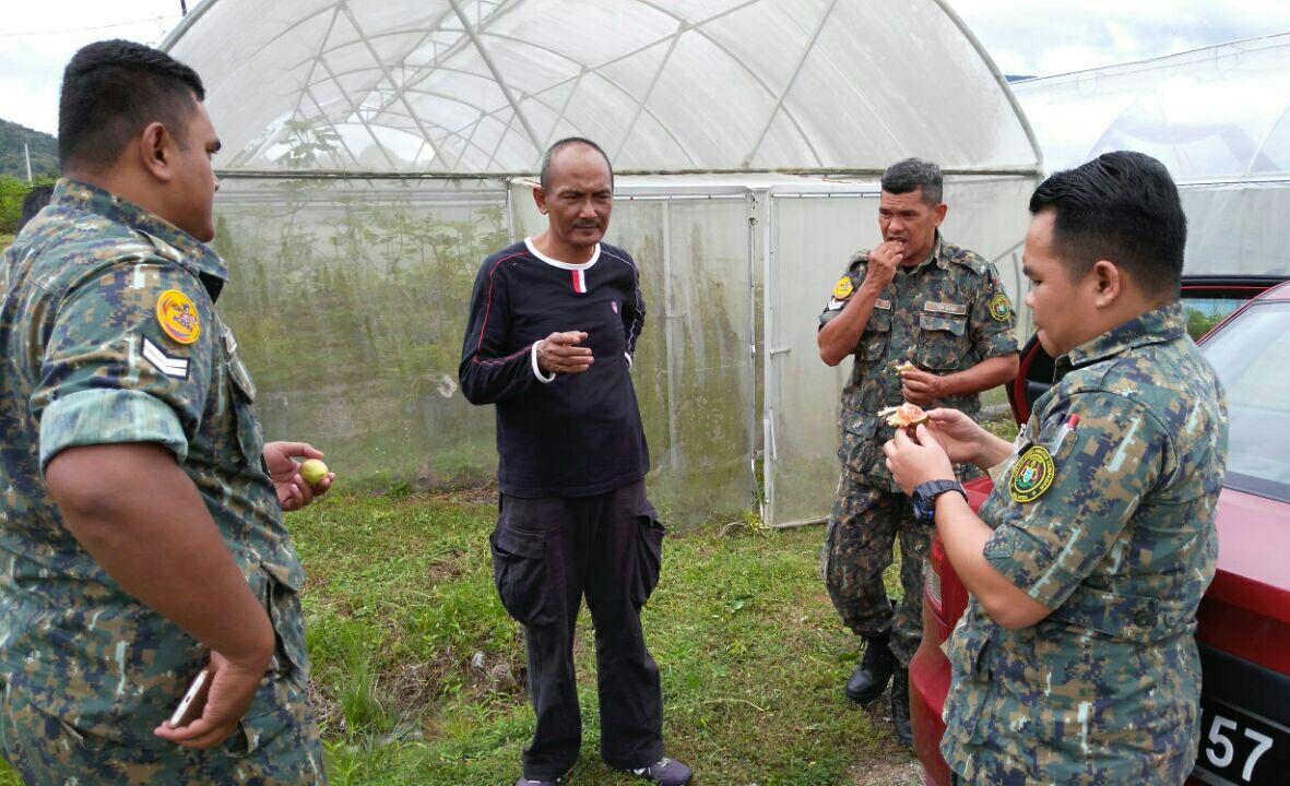 anggota agensi kawalan sempadan menikmati buah tin segar
