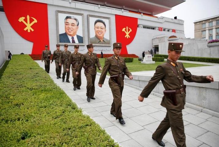 askar korea utara berjalan di hadapan gambar pemerintah