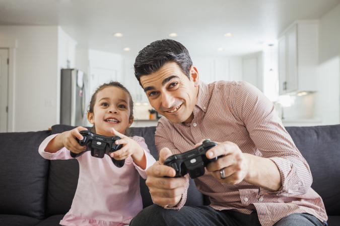ayah bermain video game dengan anak perempuan