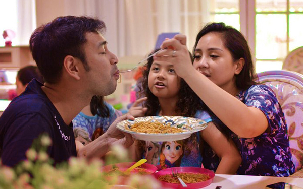 ibu ayah dan anak sedang makan bersuap