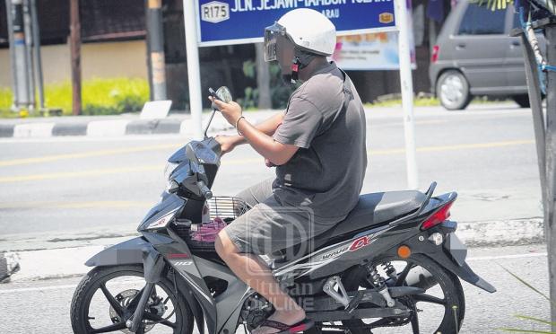 main henfon ketika menunggang motosikal