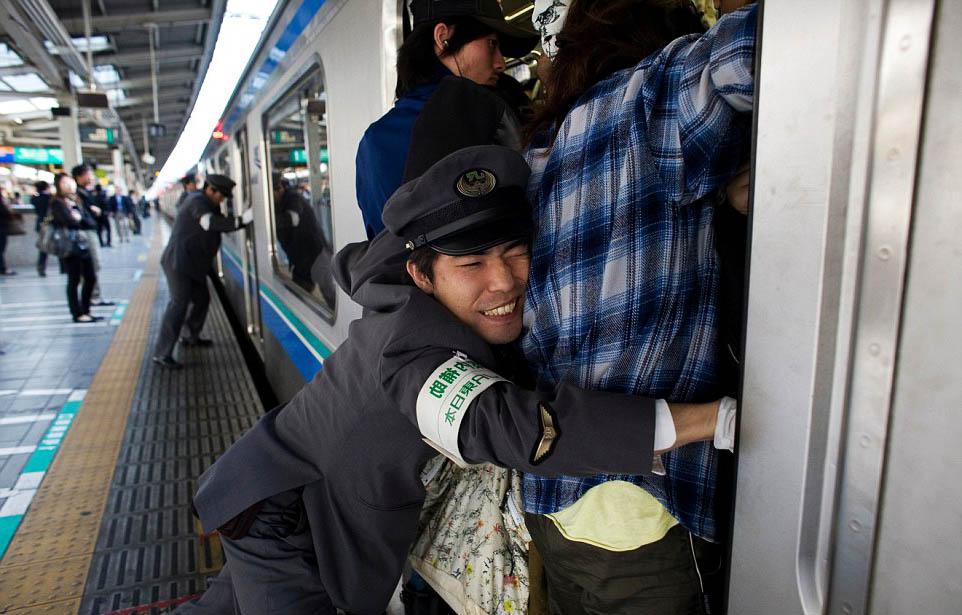 pegawai terpaksa menolak penumpang masuk ke dalam kereta api di jepun
