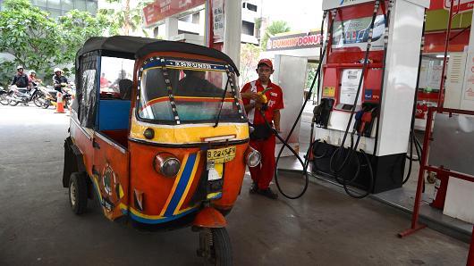 pekerja mengisi minyak di pam