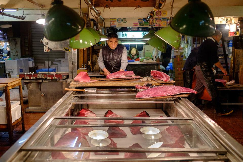 pemborong memotong ikan tuna kepada bahagian lebih kecil untuk dijual kepada restoran sushi