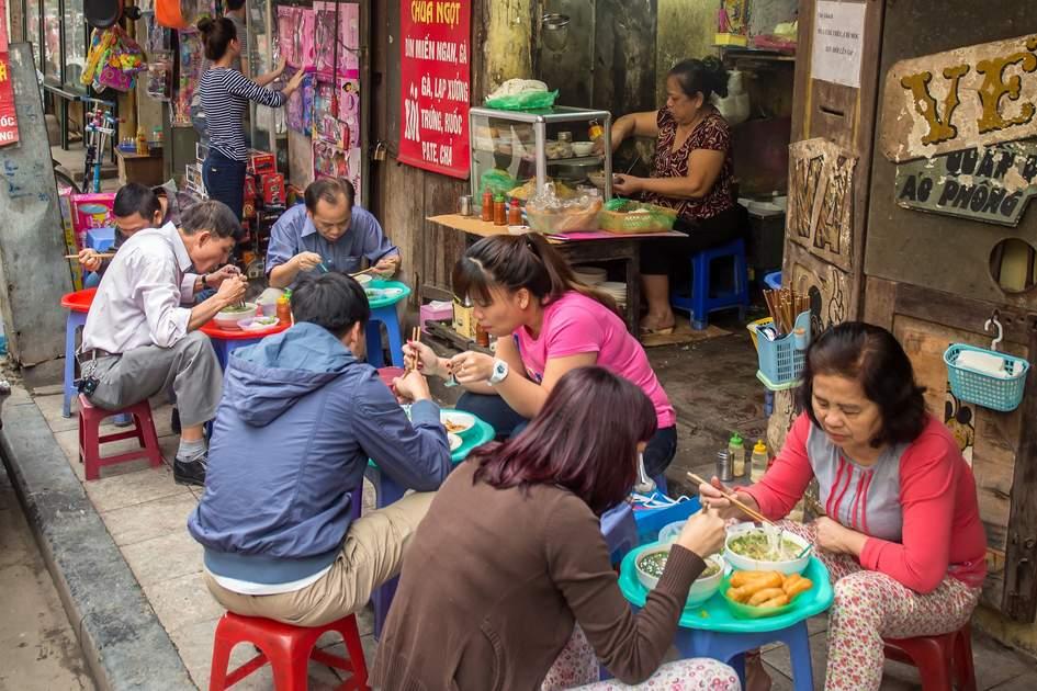 penduduk tempatan menikmati makanan di gerai jalanan