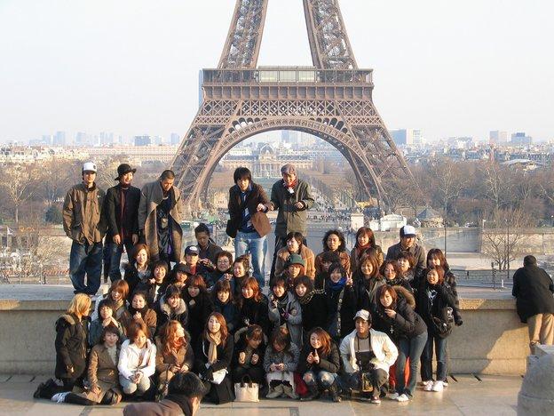 pengunjung mengambil gambar berlatarbelakangkan menara eiffel