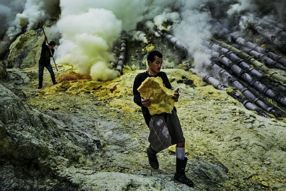 salah seorang pelombong mengangkat sulfur
