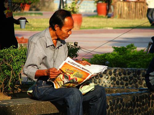 seorang lelaki filipina sedang membaca akhbar
