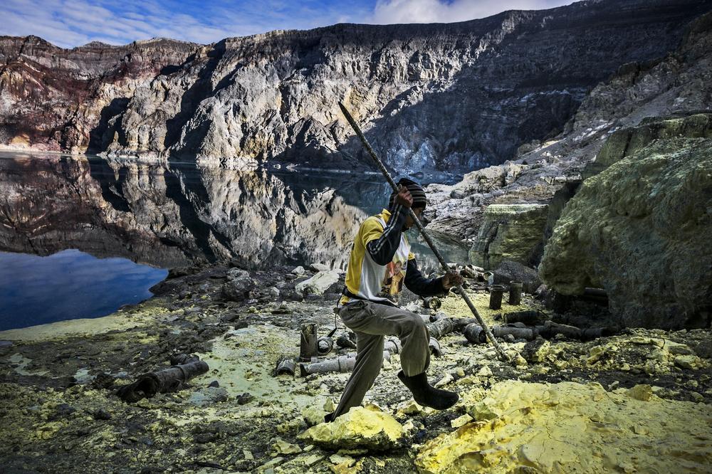 seorang pekerja sedang memecahkan ketulan sulfur