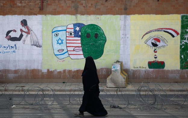 seorang wanita berjalan di depan kedutaan saudi di sanaa yaman